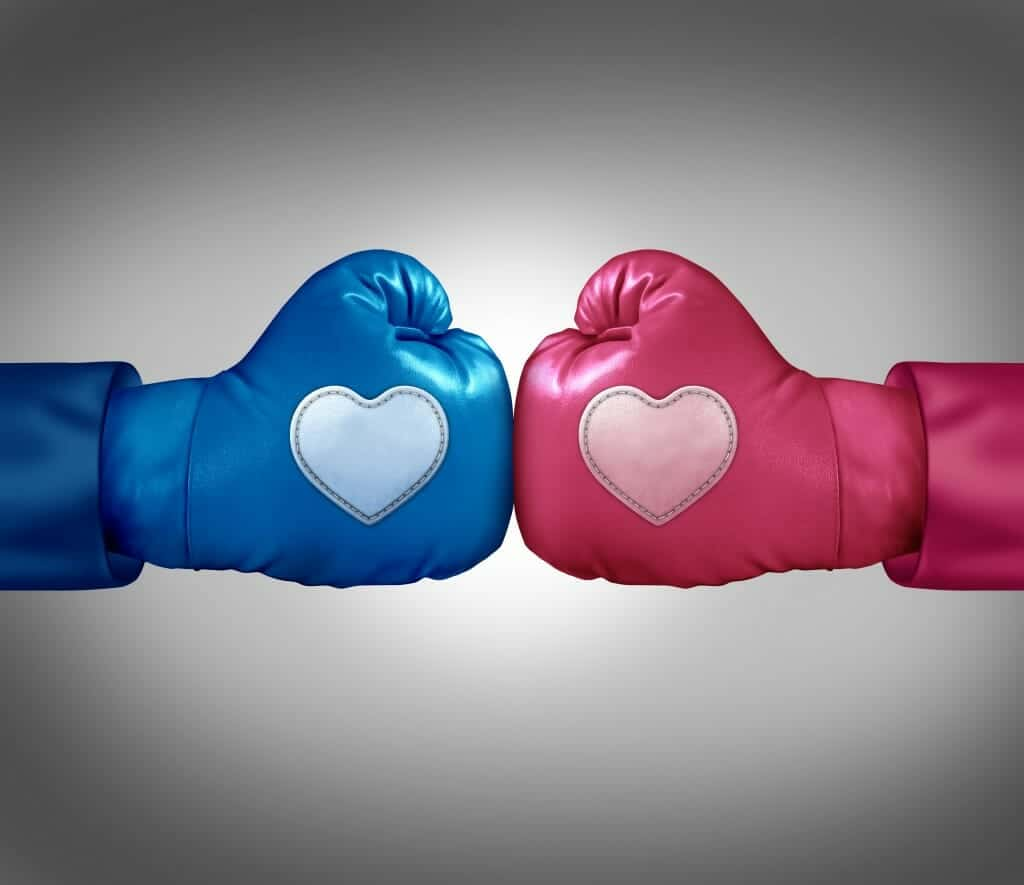 Blue and pink boxing gloves with hearts on them facing off.