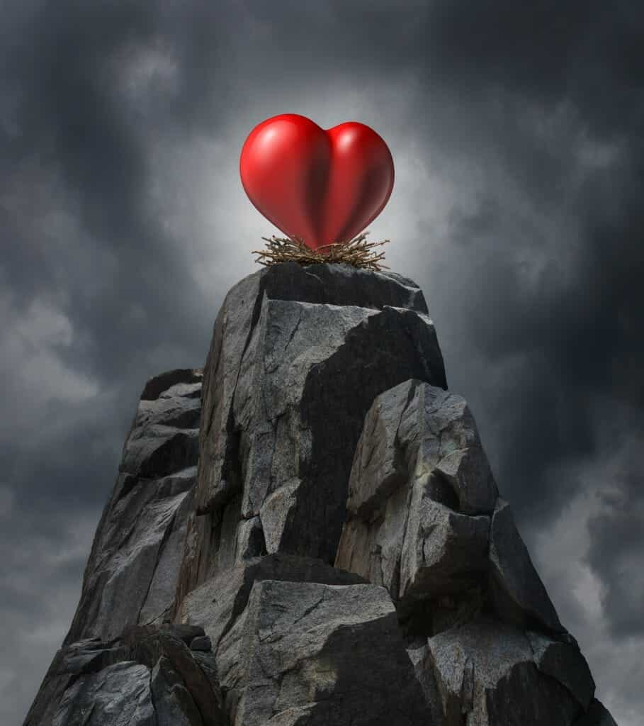 Love and relatinship challenge problem concept and romantic life trouble or heartache and loneliness as a red heart sitting high on cliff in a nest as a long distance dating symbol or finding romance.