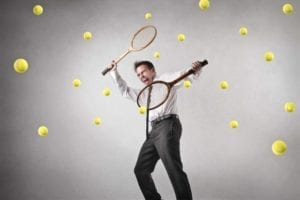 Man holding tennis rackets in each hand wildly batting multiple tennis balls coming at him. Divorce stress
