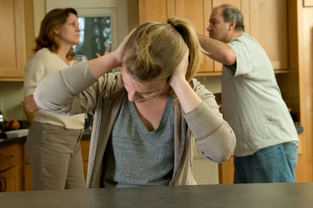 Young girl covering her ears as her parents argue in the background.