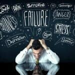 """Emotional Health - Upset man staring at table while words """"Stress"""" """"Failure"""" """"Anger"""" etc hover above his head"""