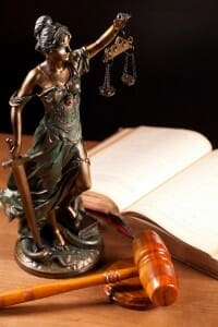 Bronze lady of justice statue next to open law book and gavel.