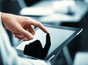 Hand with finger on a tablet computer.