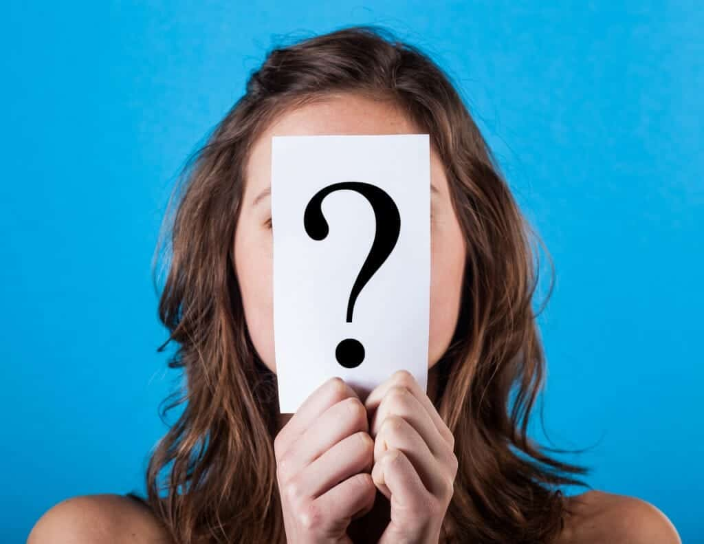 Woman thinking about divorce and holding a paper with a Big Question Mark on it,.