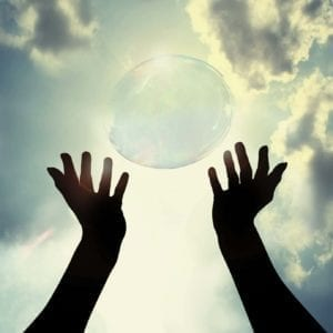 Hands reaching up to a blue sky, releasing a bubble. Sun is shining.