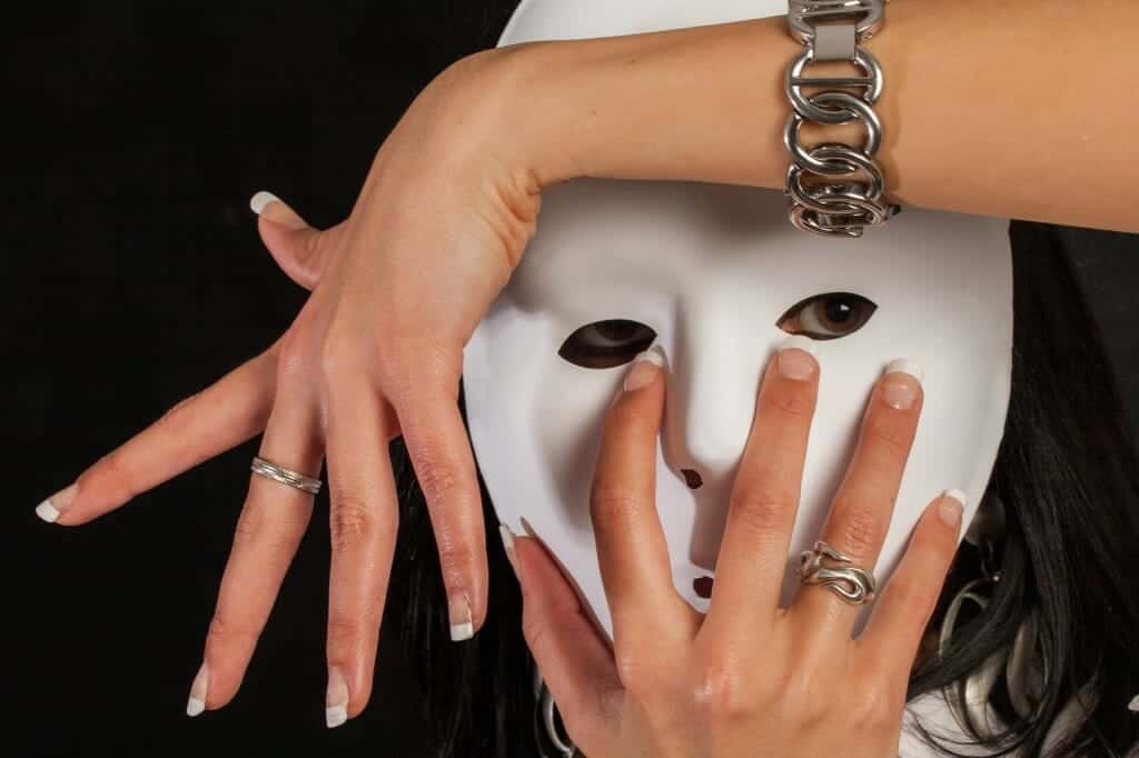 Woman hiding behind white mask with hands around her face.