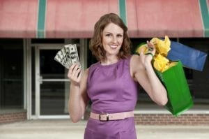 Woman Shopping, holding up money and purchases.