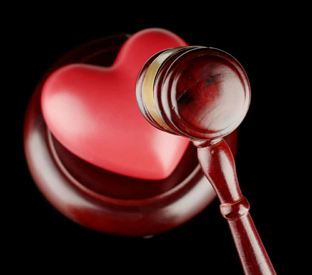Red heart about to be pounded by judge's gavel.