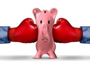pink piggy bank getting squeezed from both sides by red boxing gloves