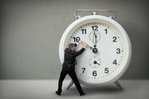 Man tugging at the hands of a giant alarm clock. Make time go backwards.