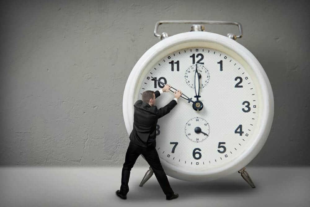 Man tugging at the hands of a giant alarm clock.