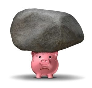 Sweating pink piggy bank with a big rock on it.