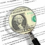 Prenuptial Agreement with a magnifying glass showing money underneath