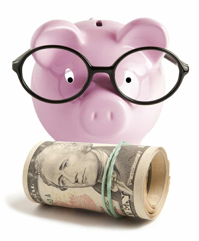 Pink piggy bank wearing glasses looking down at a roll of money.