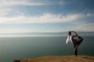 DIvorce and yoga. Woman doing yoga on a mountaintop