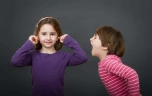 Small boy screaming at young girl with her ears plugged.