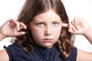 How NOT to tell your kids about divorce. Small sad girl with her fingers in her ears.