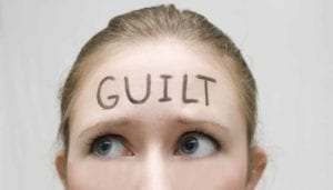 "Close up of a nervous woman with the word ""Guilt"" written on her forehead."