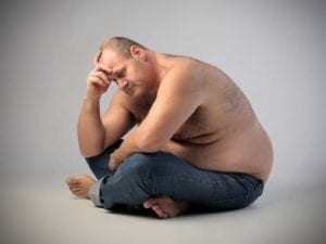 Obese man holding his head and looking depressed