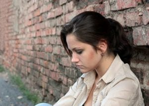Sad, guilty woman sits next to a brick wall - Divorce guilt trip