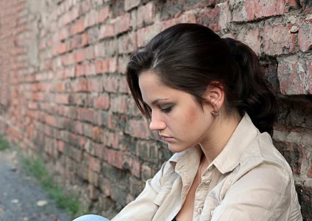 Sad woman sitting against a brick wall.