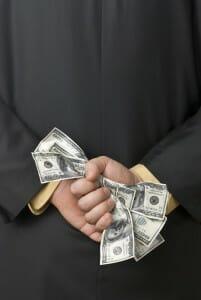 Man holding 100 dollar bills behind his back.