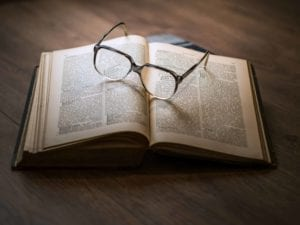 Pair of glasses sitting on top of an open book.
