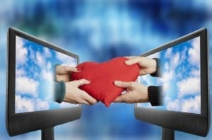 Online Dating - Computer screens facing each other with man and woman's hands coming out and holding a heart pillow
