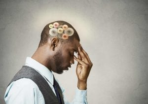 African American man holding his forehead while wheels turn inside his brain