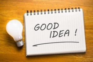 """Note pad with the word """"Good idea"""" on it, next to a light bulb"""