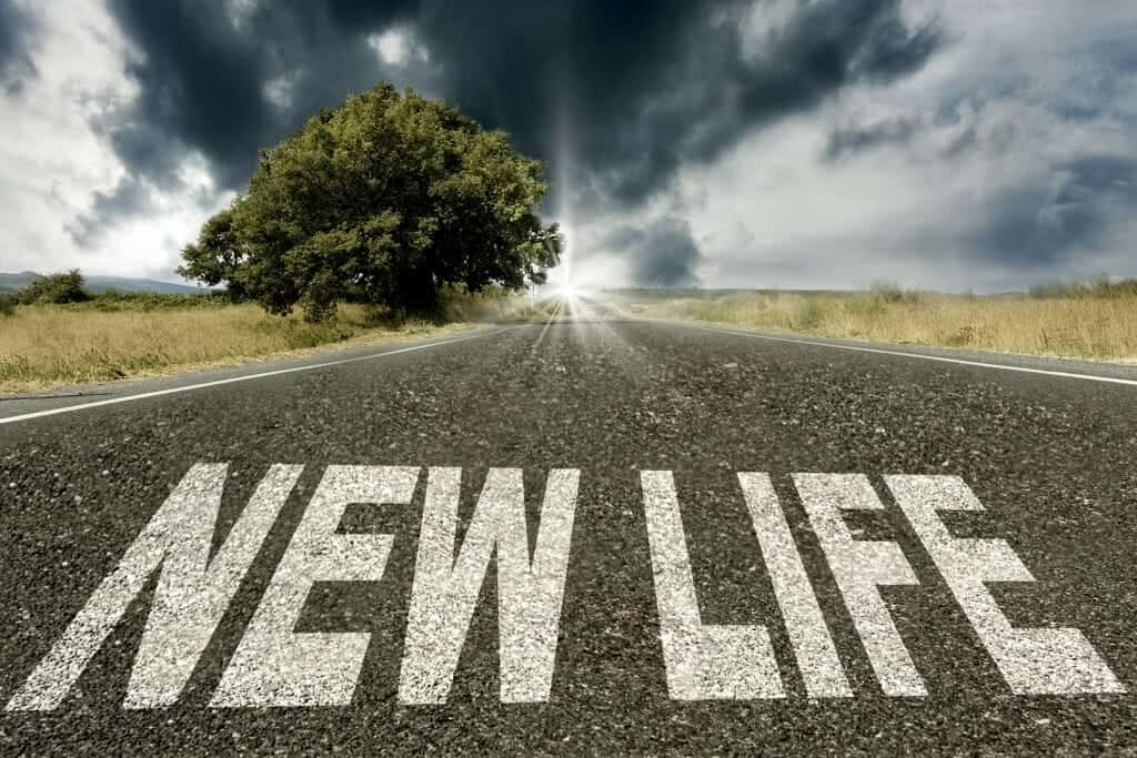 """Close up of the words """"New Life"""" on road leading into the light."""