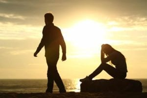 Irreconcilable differences: Man walking away from distraught woman on the beach in the sunset.