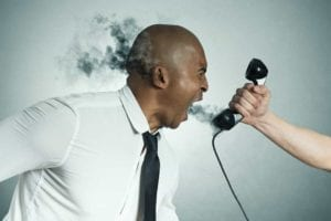 African American man screaming into telephone with smoke coming out of his head.