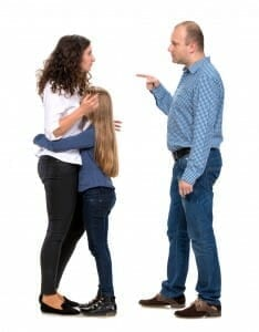 Parents argue while young girl clings to her mother.