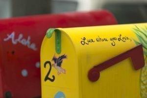 "Red and yellow rustic mailboxes. ""Live Where You Love"" is written on one of them."