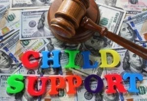 """Multi-colored plastic letters spelling """"child support"""" on top of a pile of $100 bills with a judge's gavel."""