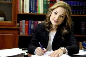 Pretty female attorney taking notes in a library of law books.