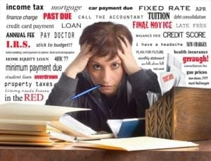 Harried woman surrounded by paperwork with words IRS, Past Due, Overdrawn, Credit Score etc in the background.