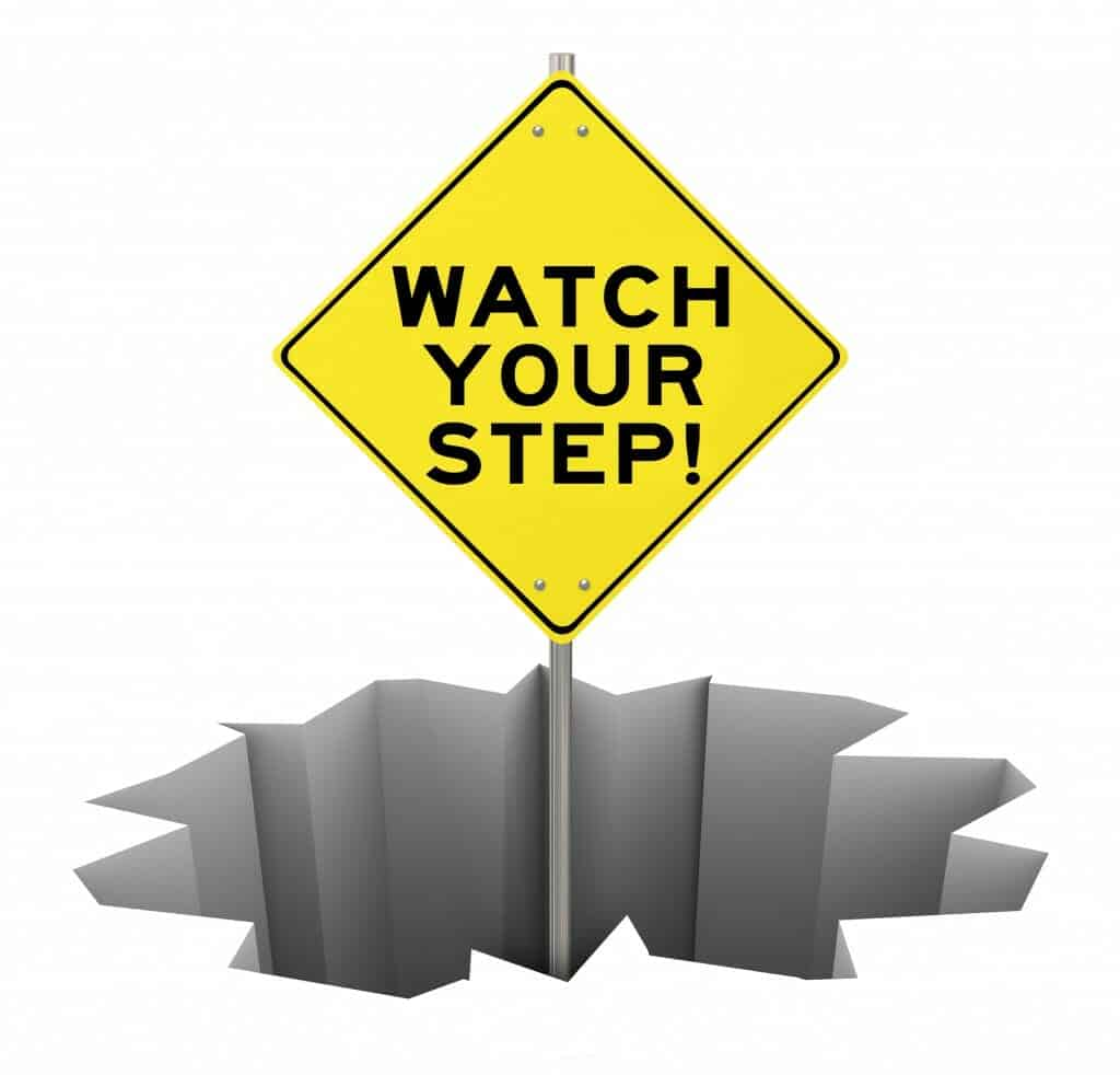 """Yellow """"Watch Your Step"""" sign coming out of an open crater."""