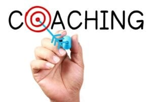 "Hand drawing an arrow in the word ""Coaching"" with a target in the ""O."""