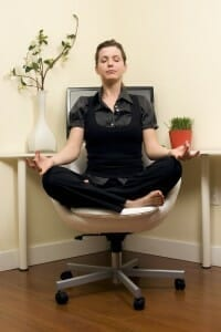 Working woman meditating in front of her computer.