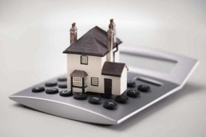 A house is expensive! Toy house sits on top of a calculator.
