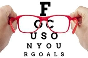 Hand holding red glasses. Behind is an eye chart with letters spelling: FOCUS ON YOUR GOALS.