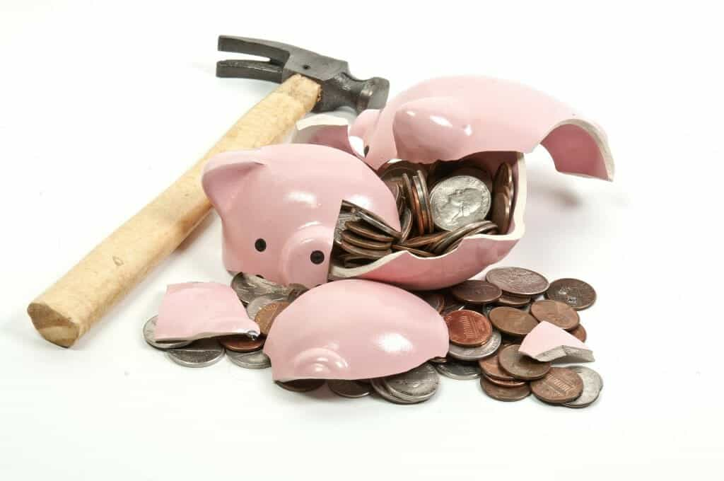 Broken piggy bank filled with coins and a hammer next to it.