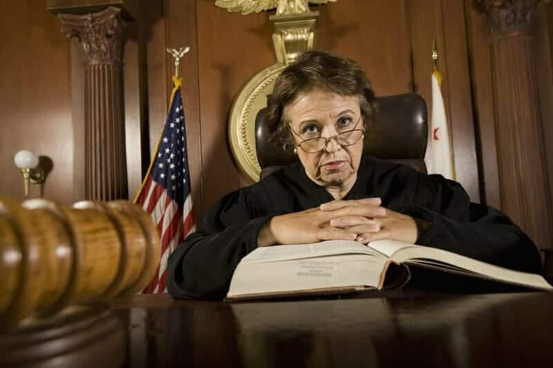 Stern looking older judge looking down from the bench with a law book in front of her.