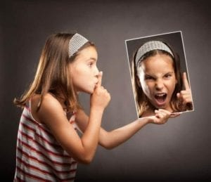 Young girl shushing a photo of herself screaming