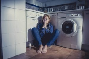 Lonely, upset woman sitting alone in laundry room.