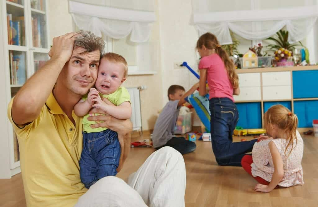 Parenting after divorce: Overwhelmed father sits among children playing