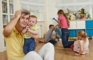 Overwhelmed father sits among children playing