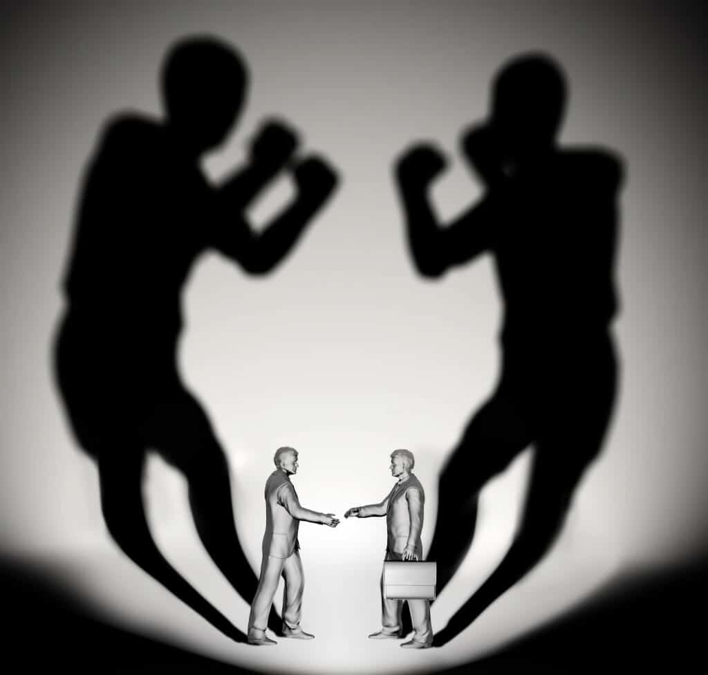 Business men shaking hands while their shadows box with each other.